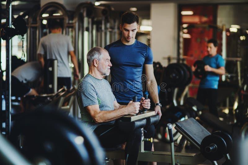 Un uomo senior con un giovane istruttore che fa esercizio di allenamento di forza in palestra immagine stock