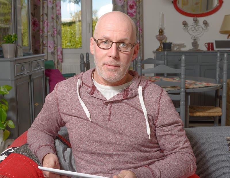 Un uomo senior con una compressa digitale fotografia stock libera da diritti