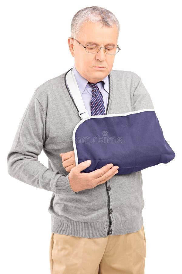 Un uomo senior con una posa rotta del braccio immagini stock