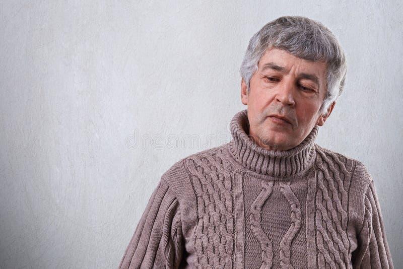 Un uomo senior triste che sembra il basso premuroso si è vestito in maglione Un uomo anziano wrinlked con capelli grigi che pensa immagini stock