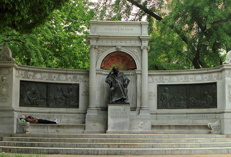Un uomo senza tetto che prende un pelo sul banco di Samuel Hahnemann Monument fotografie stock