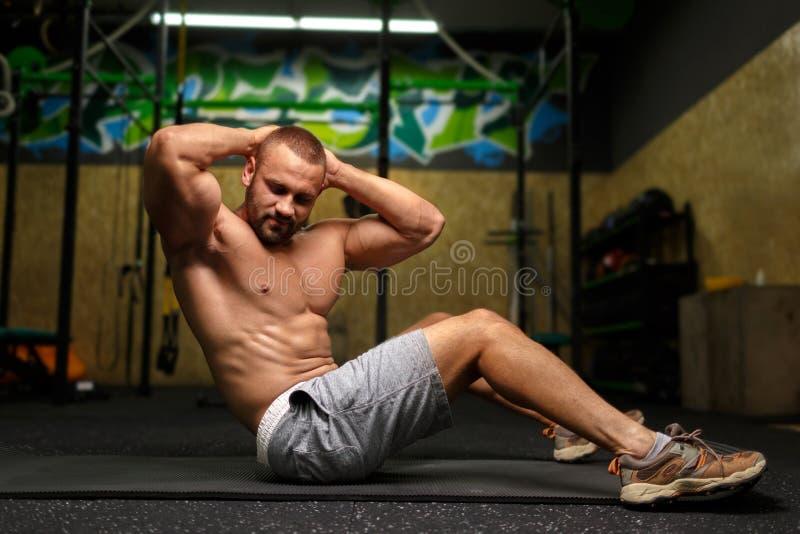 Un uomo sexy che fa un esercizio su un pavimento e su un fondo di una palestra Concetto di sport, di addestramento e di esercizi immagini stock