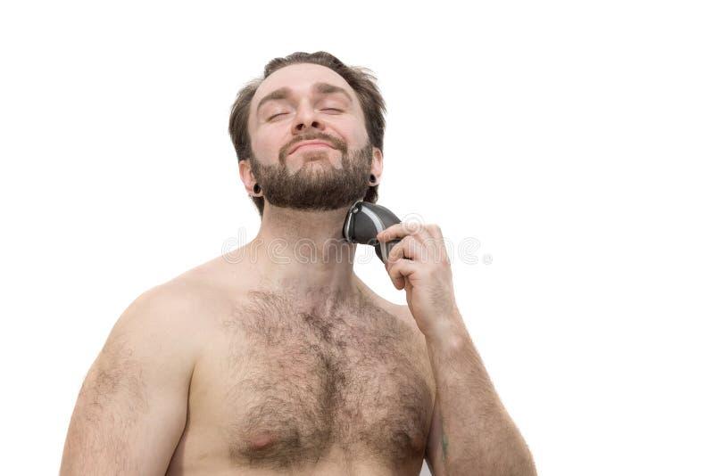 Un uomo si rade contro un fondo bianco fotografia stock