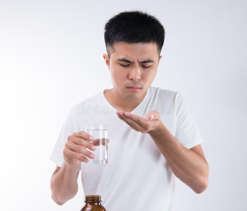 Un uomo si sente male dopo il cibo del troppo gnocco delizioso di zongzirice e sta andando mangiare la medicina dello stomaco su  fotografia stock