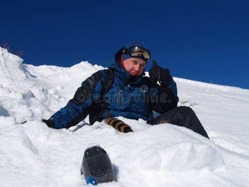 Un uomo si siede nella neve fotografia stock libera da diritti