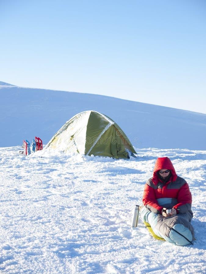 Un uomo si siede in un sacco a pelo vicino alla tenda ed alle racchette da neve immagine stock