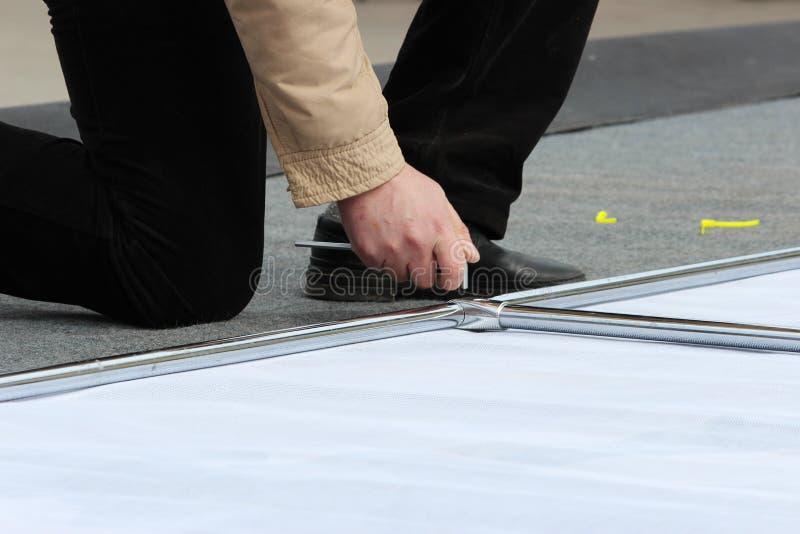 Un uomo smantella la costruzione del metallo con un cacciavite esagonale durante lo smantellamento della scena dopo la festa fotografia stock