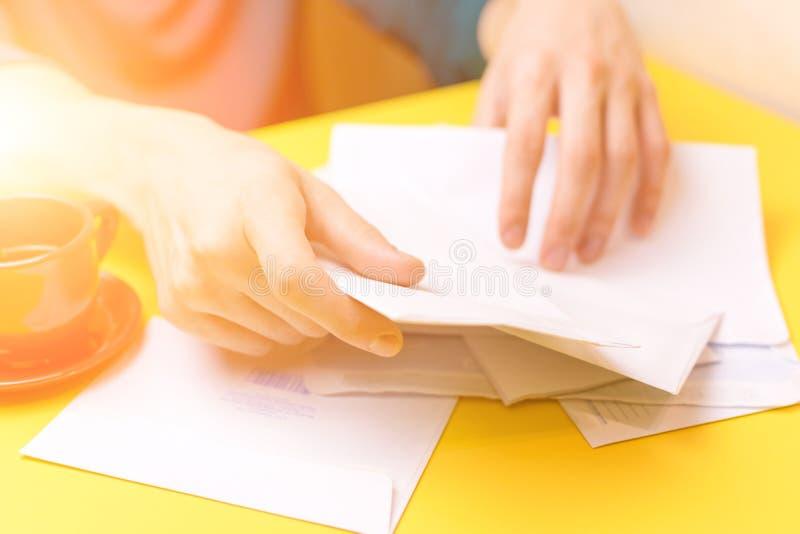 Un uomo smista la corrispondenza Il maschio passa le buste su un fondo giallo, una tazza di caffè rossa immagini stock libere da diritti
