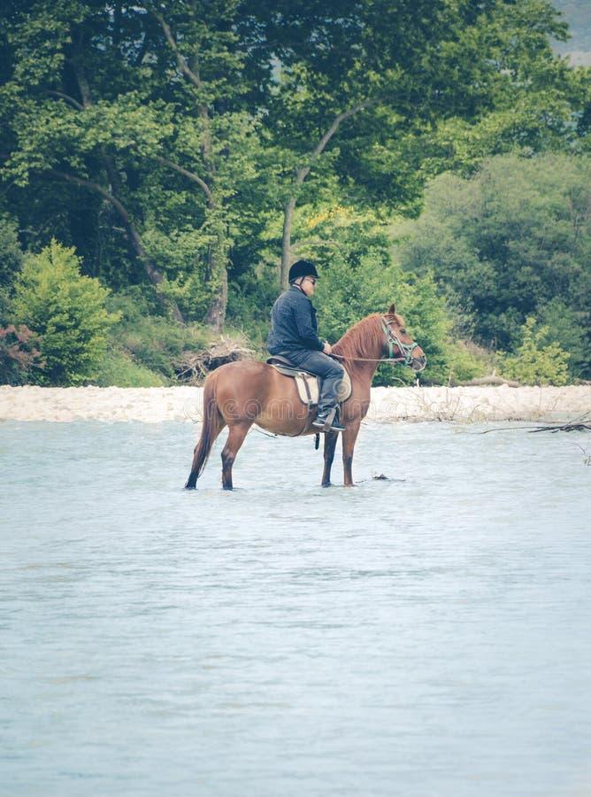 Un uomo solo che attraversa un fiume con un cavallo Le molle di Acheronte è una destinazione popolare fra i Greci ed offre varie  fotografie stock