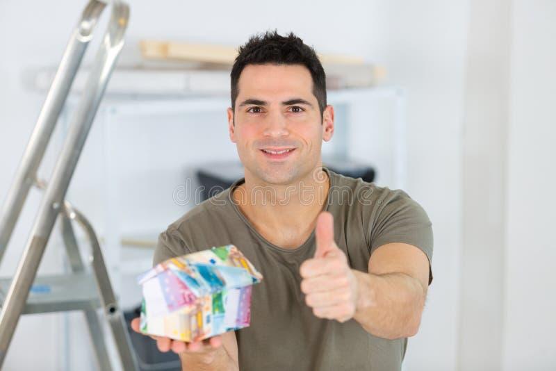 Un uomo sorridente con una modella di casa che gestiva i pollici immagini stock libere da diritti