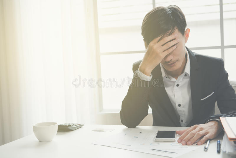 Un uomo sottolineato di affari tiene la sua testa nella disperazione immagini stock