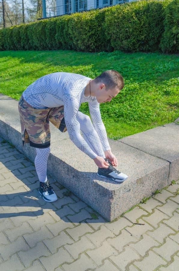 Un uomo in sport bianchi uniforma, scaldandosi fotografia stock libera da diritti