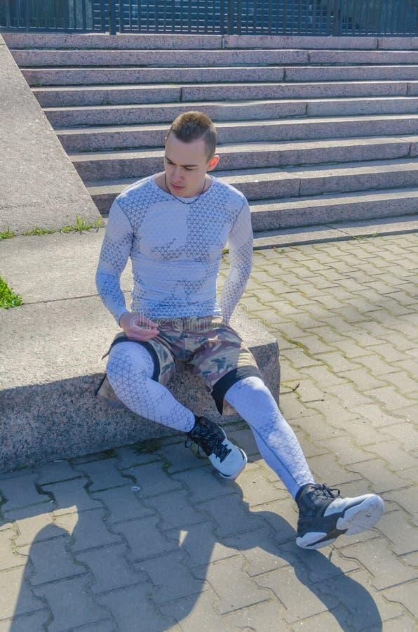 Un uomo in sport bianchi uniforma, scaldandosi immagini stock