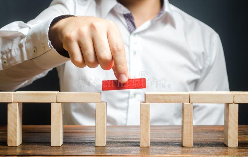 Un uomo sta completando la costruzione di un ponte Costruire ponti, creare connessioni e contatti utili Miglioramento e sviluppo fotografia stock