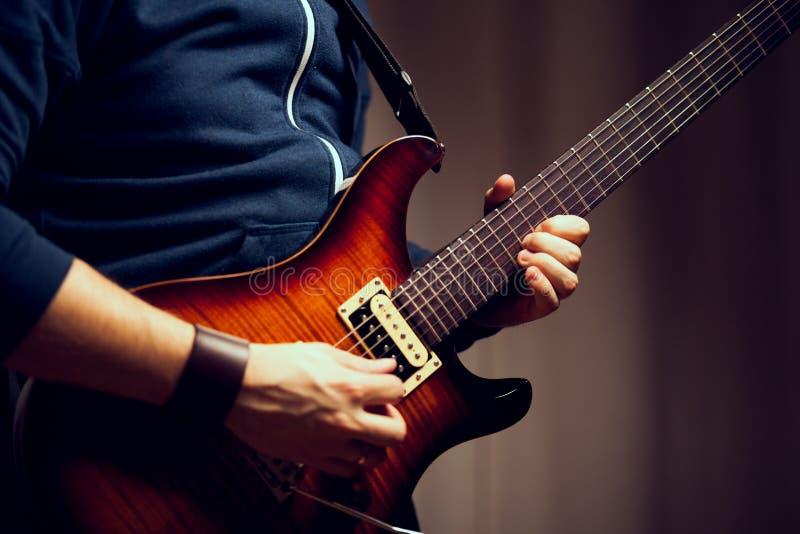 Un uomo sta giocando la chitarra elettrica fotografia stock libera da diritti