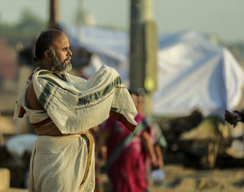 Un uomo sta pregando a Gange nel primo mattino fotografia stock libera da diritti