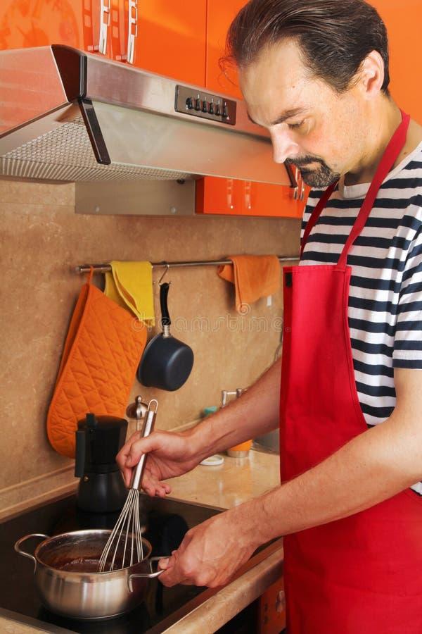 Un uomo sta preparando la crema del cioccolato per il dolce classico di Sacher fotografia stock