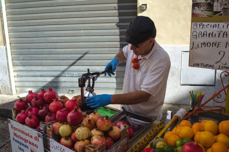 Un uomo sta schiacciando il melograno nel mercato storico del capo a Palermo, Sicilia immagini stock