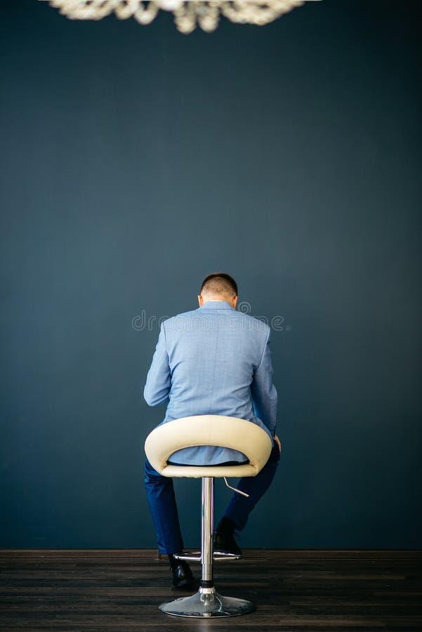 Un uomo sta sedendosi in una sedia bianca contro una parete blu Vista dalla parte posteriore fotografia stock