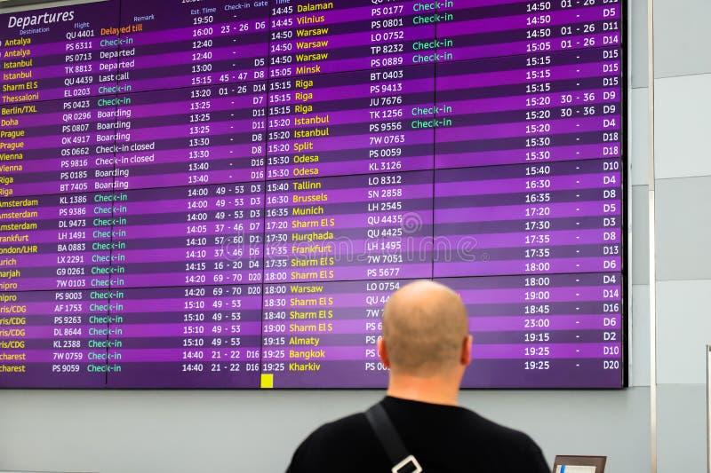 Un uomo sta stando davanti al bordo di informazioni per gli arrivi e le partenze Supporto all'aeroporto, ferrovia di informazioni immagine stock