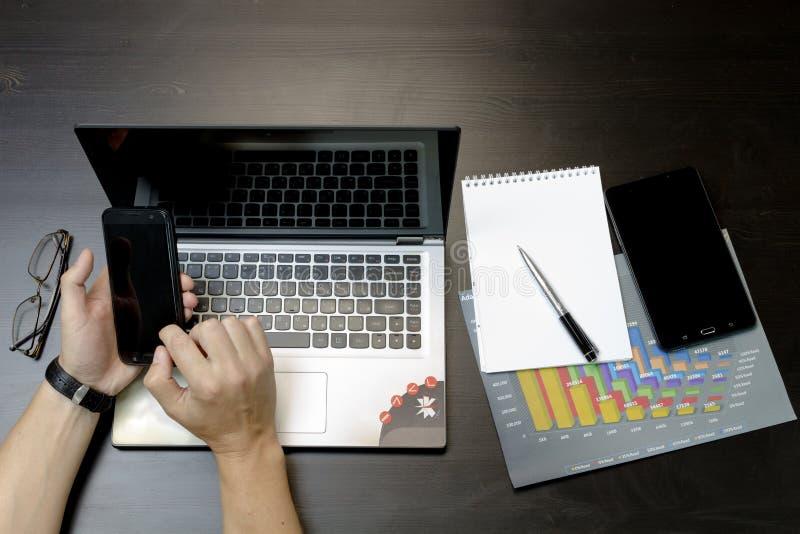 Un uomo stampa su un computer portatile, trovantesi accanto al telefono, glasse della compressa fotografia stock