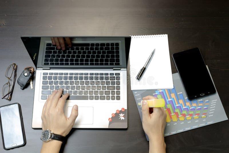 Un uomo stampa su un computer portatile, trovantesi accanto al telefono, glasse della compressa immagini stock libere da diritti