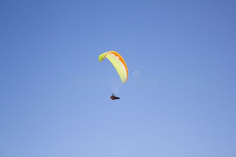 Un uomo su un aliante bianco arancio verde in una gondola contro un cielo blu pulito fotografia stock libera da diritti