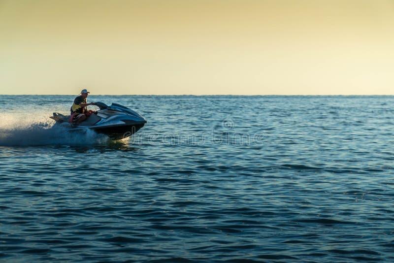 Un uomo su un aquabike contro un tramonto sul mare immagini stock