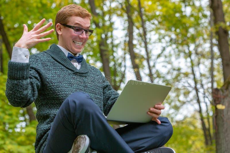 Un uomo su un piedistallo che finge di essere una statua con un computer portatile a disposizione con l'espressione come l'idea l fotografia stock