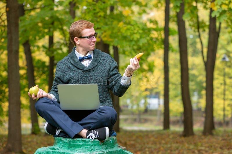 Un uomo su un piedistallo che finge di essere una statua nella posa di un filosofo prima della scelta una mela o della banana in immagine stock