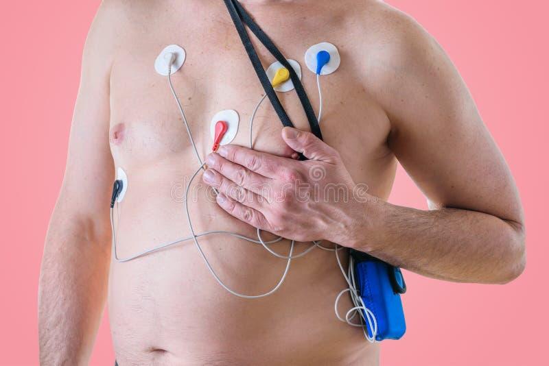 Un uomo subisce un esame del cuore e tiene la sua mano sopra il suo seno sinistro il metodo della capezza fotografia stock