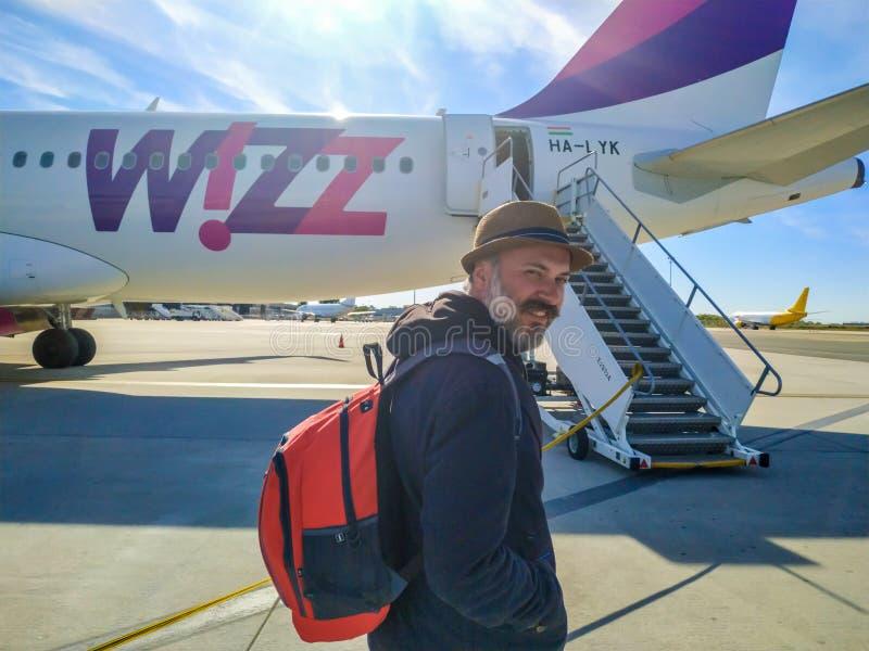 Un uomo sui precedenti della linea aerea piana di WIZZ AIR all'aeroporto internazionale a Varsavia, Polonia immagine stock