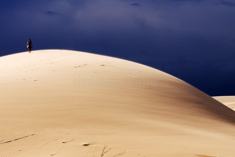 Un uomo sulla cima della collina di sabbia immagini stock