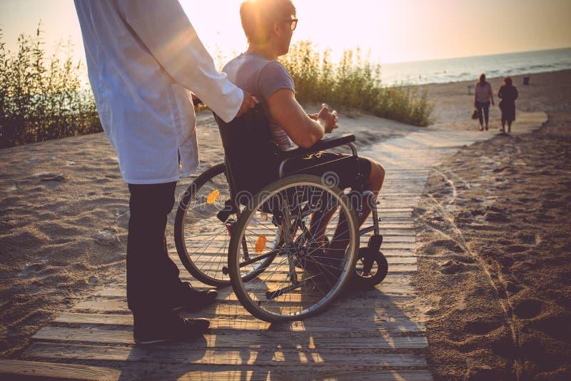 Un uomo sulla sedia a rotelle e sulla sua infermiere fotografia stock