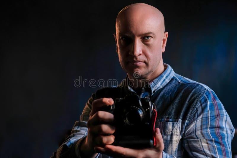 Un uomo sviluppato in una camicia con una macchina fotografica in sue mani immagini stock libere da diritti