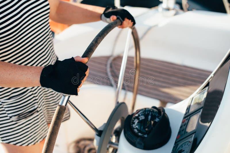 Un uomo tiene un casco del ` s dell'yacht con due mani, indossanti i guanti di estate fotografie stock libere da diritti