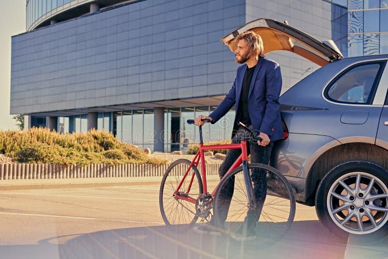 Un uomo tiene la bicicletta fissa vicino all'automobile con il tronco aperto fotografia stock