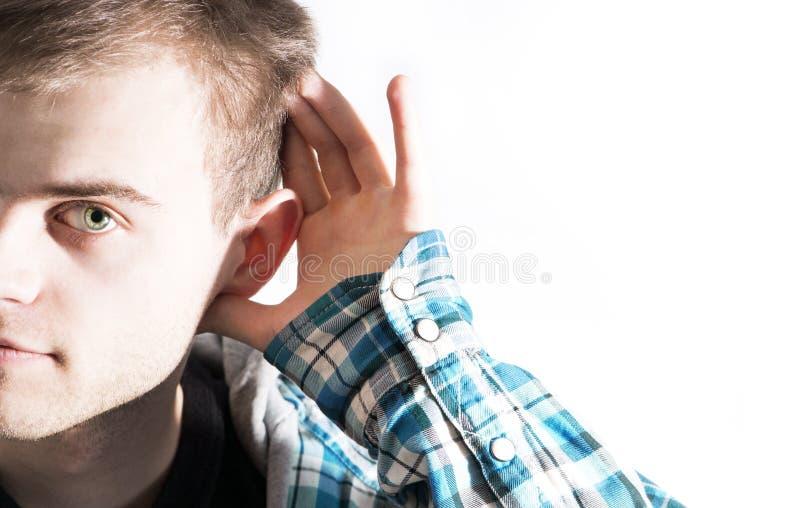 Un uomo tiene la sua mano al suo orecchio che prova a sentire qualcosa, dice fotografie stock