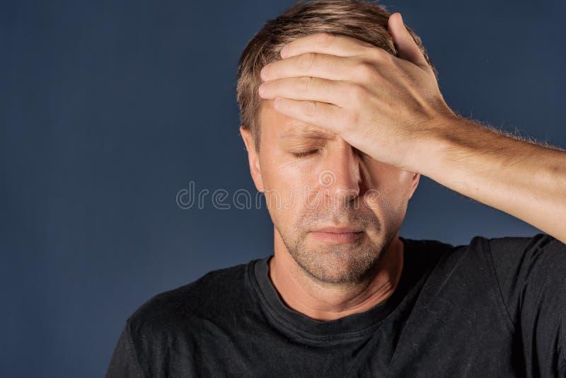 Un uomo tiene le sue mani sulla sua testa su fondo blu Emicrania e freddo fotografia stock