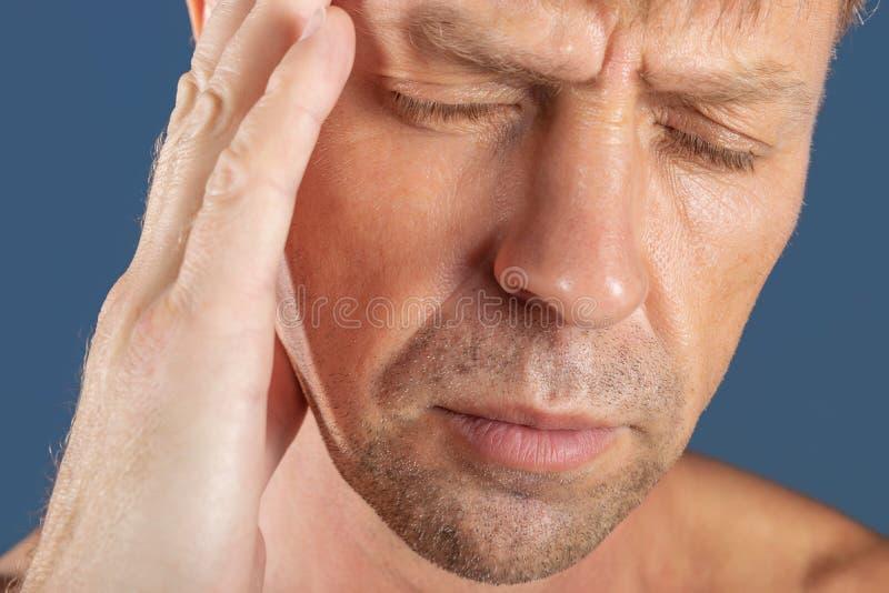 Un uomo tiene le sue mani sulla sua testa su fondo blu Emicrania o emicrania immagini stock