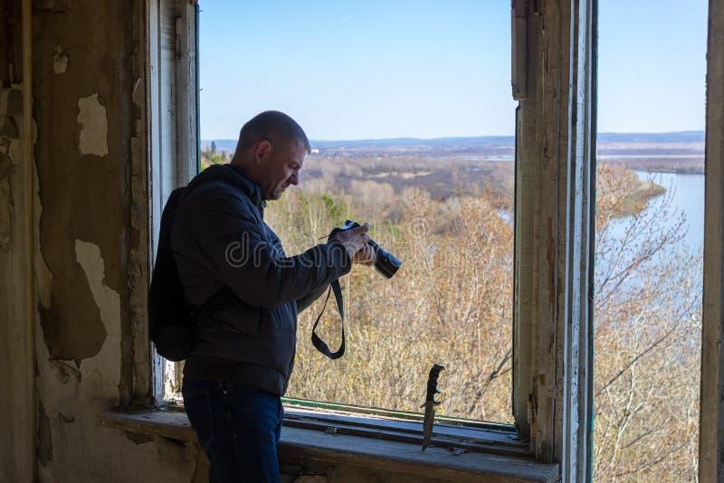 Un uomo tiene una macchina fotografica alla finestra dentro una costruzione abbandonata fotografia stock