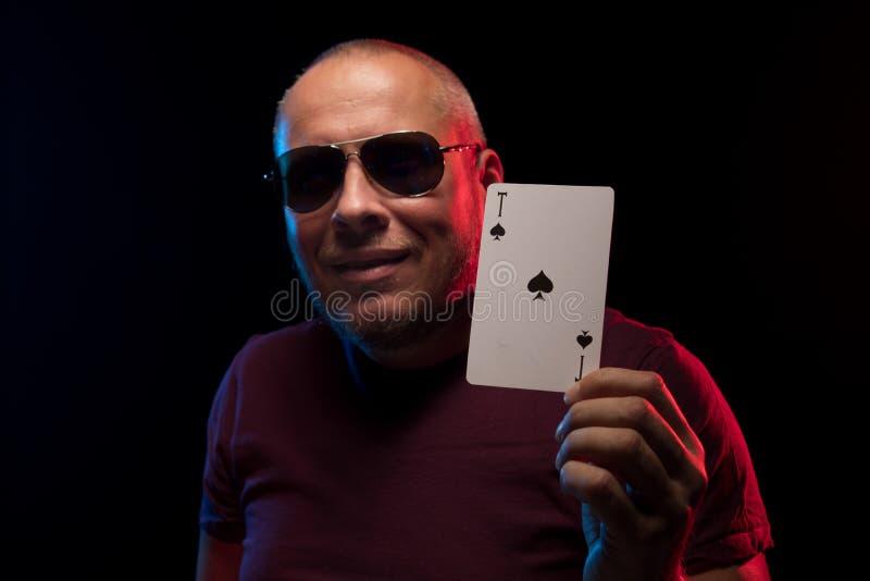 Un uomo tiene una piattaforma delle carte del gioco fotografia stock
