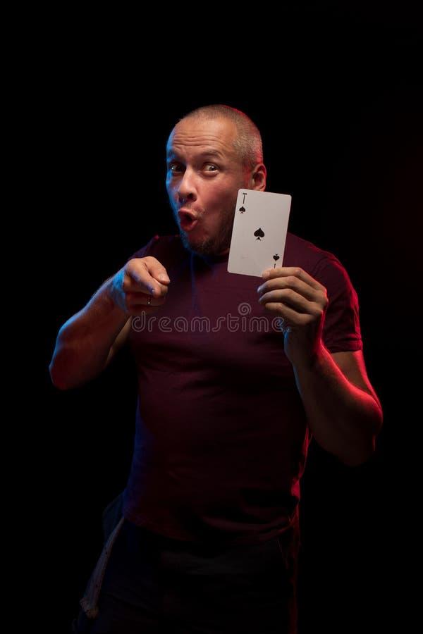 Un uomo tiene una piattaforma delle carte del gioco immagine stock