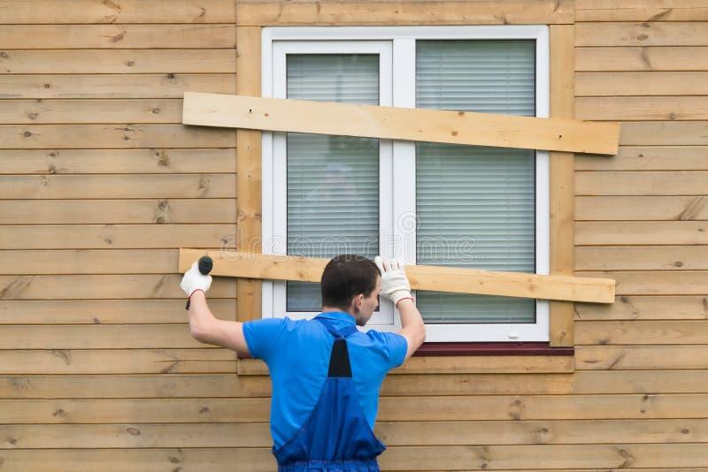 Un uomo in tute chiude le finestre con i bordi per proteggere la casa durante una partenza e l'uragano lunghi immagine stock
