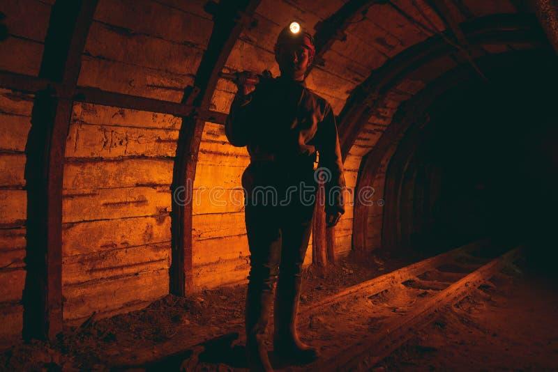 Un uomo in tute da lavoro e un casco con un martello pneumatico sulla spalla è in piedi sulle rotaie Silhouette in rosso fotografie stock
