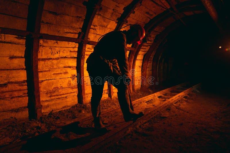 Un uomo in tute da lavoro e un casco con un martello pneumatico sulla spalla è in piedi sulle rotaie Silhouette in rosso fotografia stock libera da diritti