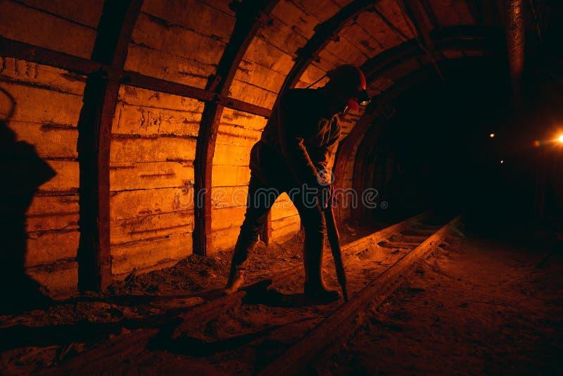 Un uomo in tute da lavoro e un casco con un martello pneumatico sulla spalla è in piedi sulle rotaie Silhouette in rosso fotografia stock