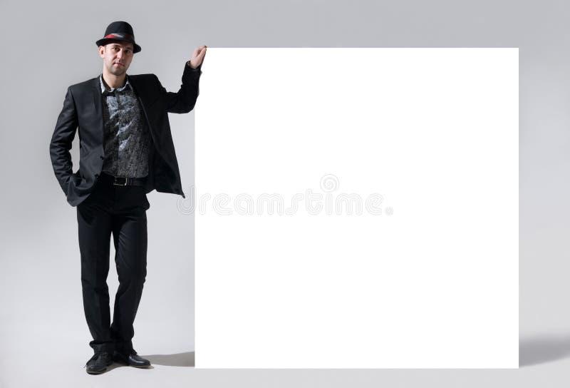 Un uomo in un cappello sta accanto ad un tabellone per le affissioni in bianco fotografia stock libera da diritti