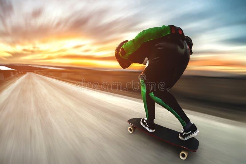 Un uomo in un vestito del cuoio e del casco, in uno scaffale all'alta velocità, guida su un longboard lungo per in discesa sopra  immagine stock libera da diritti