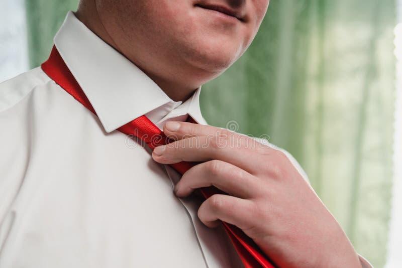 Un uomo in una camicia bianca lega un legame rosso intorno alla sua fine del collo su immagini stock